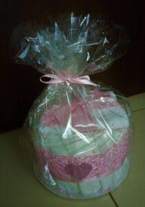 Mini csajos pelenkatorta, 17db Pampers Premium Care pelenkából, 1 db baba mosdókendővel és 1 db rózsaszín, szívecskés csillámos baba fejpánttal. Ár: 4.590,-
